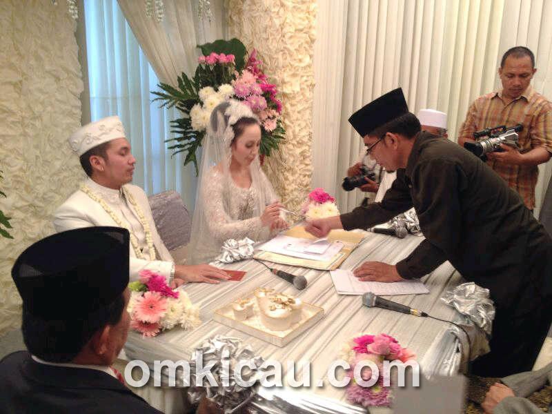 Mempelai wanita menandatangani surat nikah.