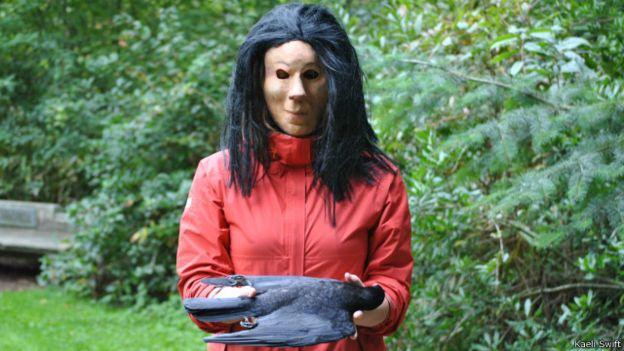 Manusia bertopeng yang membawa bangkai burung gagak saat melakukan penelitian